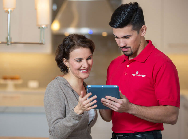 Woman looking at iPad with HomeServe repairman.
